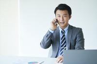 オフィスで電話をする日本人ビジネスマン