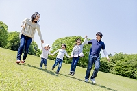 公園を手を繋いで走る日本人家族