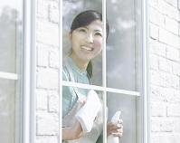 窓ふきするエプロン姿の女性