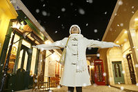 雪に喜ぶ白いコートの日本人女性
