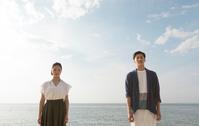 海辺に佇むカップル