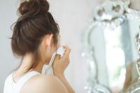 鏡を見て顔を拭く日本人女性