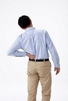 腰痛で腰に手をやる日本人男性