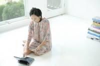 床の上でノート型パソコンを開く女性