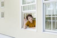 窓から手を振る笑顔の日本人のシニア女性