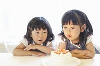 ケーキのキャンドルの火を吹き消す女の子