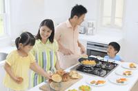 明るいキッチンで朝食を作る家族