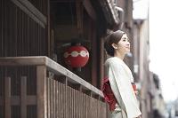 木造の店の前に立つ着物の日本人女性