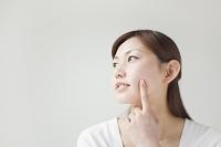 目を閉じて顔に指をあてる若い日本人女性