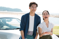 オープンカーにもたれる笑顔のカップル