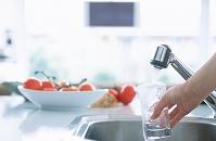 グラスで水を注ぐ手