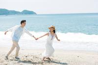 砂浜を走るカップル