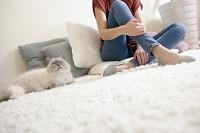 カーペットに座る外国人女性と猫