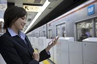 地下鉄のホームでスマートフォンを見るビジネスウーマン