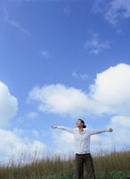青空と草原に手を広げて立つ日本人女性