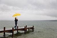 桟橋で傘を持つ少年