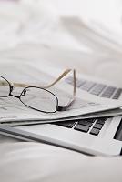 ベッドの上のノートパソコンと眼鏡
