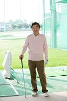 ゴルフ場に立つ熟年男性