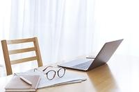 テーブル上のノートパソコンと眼鏡