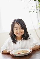 笑顔の女の子と野菜スープ
