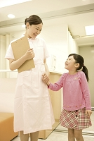 待合室で手を繋ぐ看護師と子供3