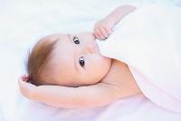 白い毛布を噛むハーフの赤ちゃん
