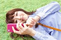 寝転んで携帯を操作する日本人女性