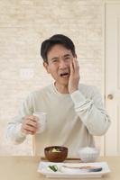 歯痛に顔をゆがめる中年日本人男性