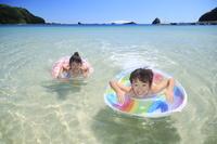 浮き輪を使って泳ぐ兄妹