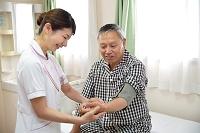 血圧と脈拍を測定する看護師とシニア男性