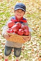 紅葉の中、リンゴを持つ6歳の日本人の男の子