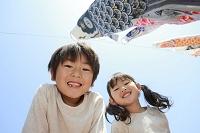 青空を泳ぐこいのぼりと日本人の子供たち