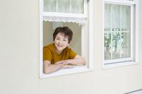 窓から顔を出す笑顔の日本人のシニア女性