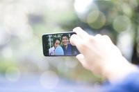 携帯電話で自撮りをする浴衣のカップル