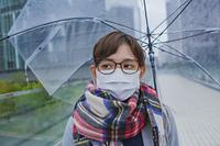 傘をさすマスク姿の女性