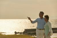 海辺で佇む日本人シニア夫婦