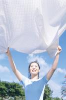 青空とテーブルクロスを広げる日本人女性