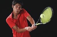 テニスする若い日本人男性