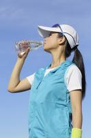 青空の下でミネラルウォーターを飲む日本人女性