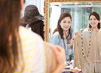 鏡を見て洋服を合わせる日本人女性