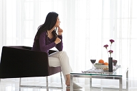 いすに座って遠くを見ている日本人女性