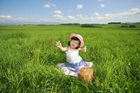 草原でピクニックをする少女