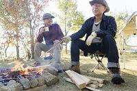 焚き火をするシニアの日本人男性