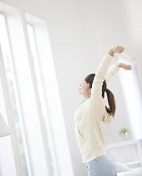 窓辺で伸びをする日本人女性