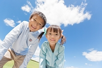 青空の下で笑っている男の子と女の子