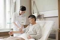 入院患者に点滴をする看護師