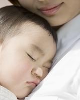 母の胸元で眠る男の子