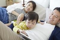 ベッドの上でくつろぐ日本人三人家族