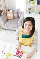 家計簿をつけている笑顔の日本人女性