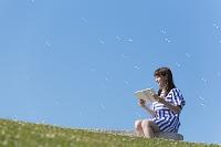 ベンチに座って本を読む笑顔の日本人女性